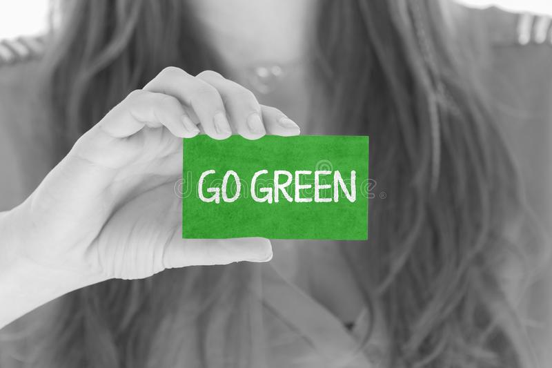 Woman showing a message: Go Green. Woman showing a small message: Go Green royalty free stock image
