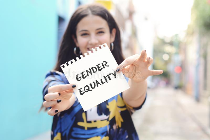 Woman showing a notepad with the text gender equality. royalty free stock image