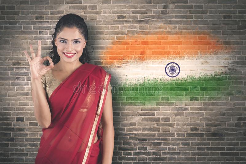 Woman showing OK sign near India flag background stock image