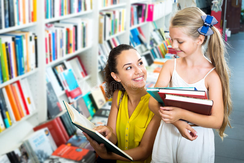 Woman showing open book to little girl stock photography