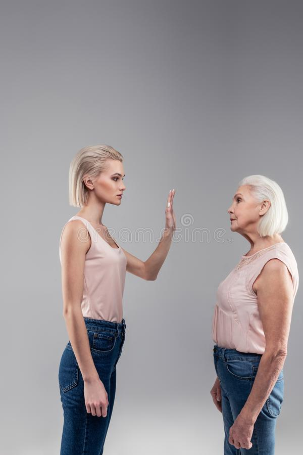 Categorical blonde short-haired beautiful girl shutting her mother up royalty free stock photo