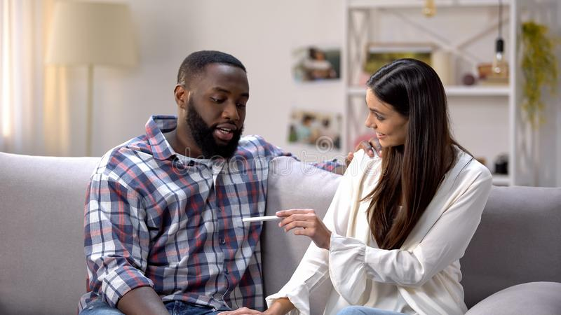 Woman showing pregnancy test to happy Afro-American boyfriend, positive result royalty free stock images