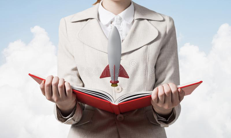 Woman showing rocket ship on open book. Rocket launch as symbol startup company. New creative project concept. Woman in white business suit on background of royalty free stock photography