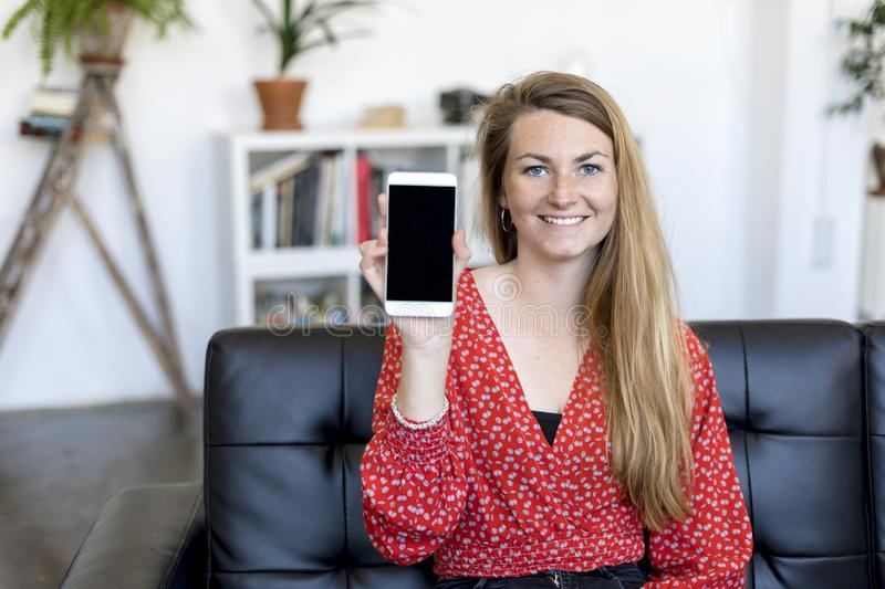 Beautiful and smiling Woman showing a screen of a smart phone sitting on a sofa royalty free stock photo