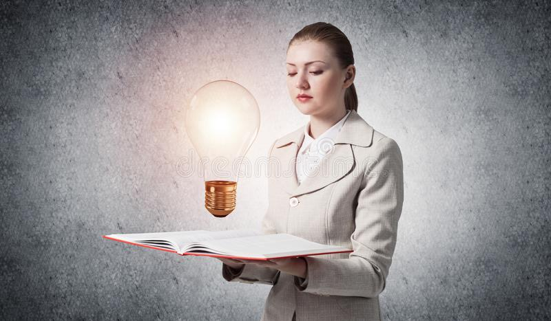 Woman showing shining light bulb on open book. Glowing light bulb as symbol creative idea generation. Woman in white business suit on background of grey wall royalty free stock photo