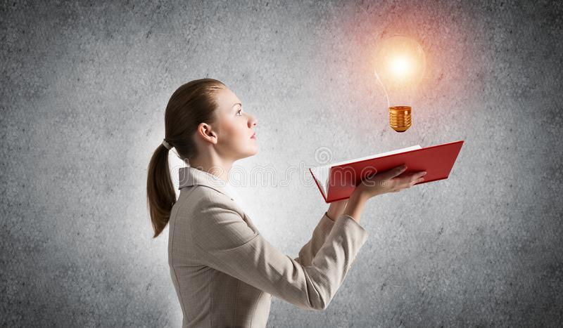 Woman showing shining light bulb on open book. Glowing light bulb as symbol creative idea generation. Woman in white business suit on background of grey wall stock photo