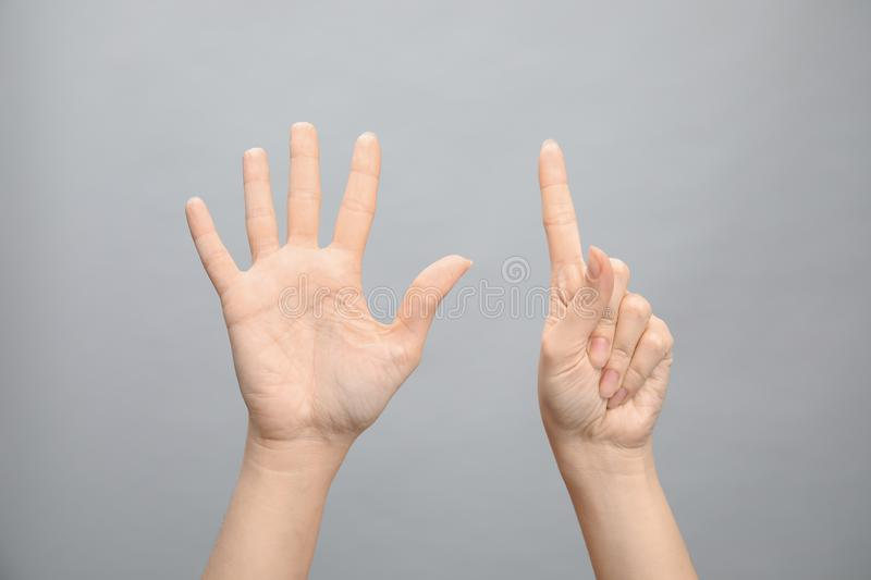 Woman showing sign six on grey background. Body language. Woman showing sign six on grey background, closeup. Body language stock image