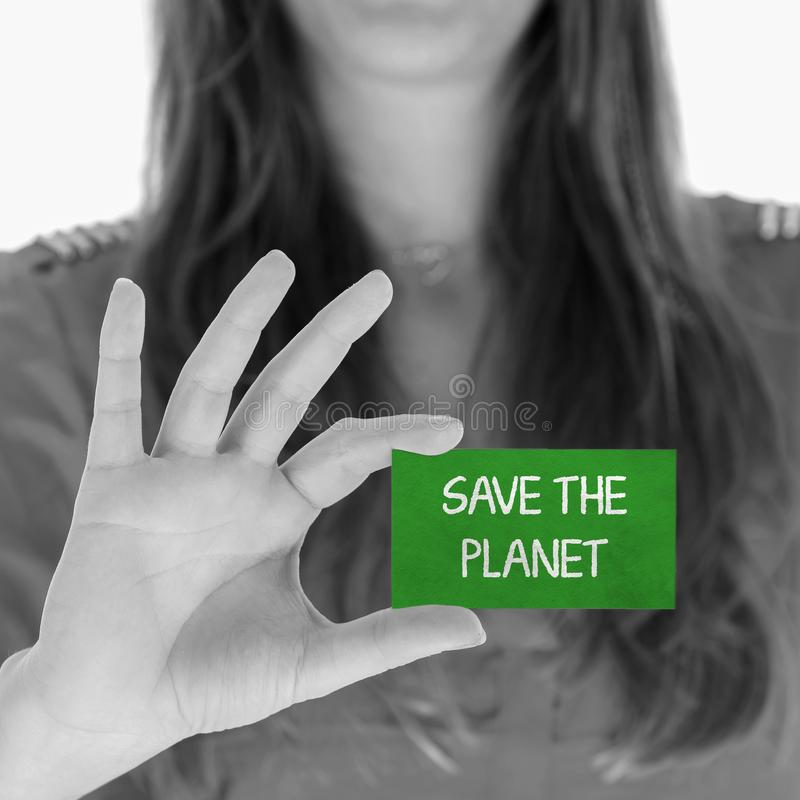 Woman showing a message: Save the planet. Woman showing a small message: Save the planet royalty free stock image