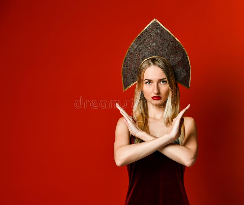 Woman showing a stop arms crossed. On a red background. stock image