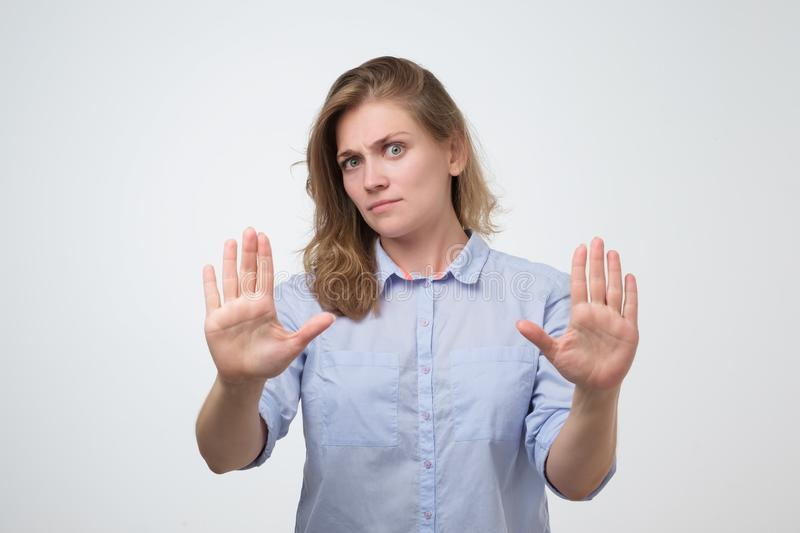 Woman showing stop or enough gesture with hand, frowning. Unhappy caucasian woman showing stop or enough gesture with hand, frowning and expressing dislike. stay stock photos