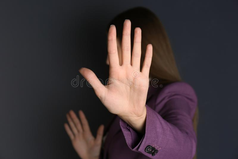 Woman showing stop gesture on dark background. Problem of sexual harassment at work stock photography
