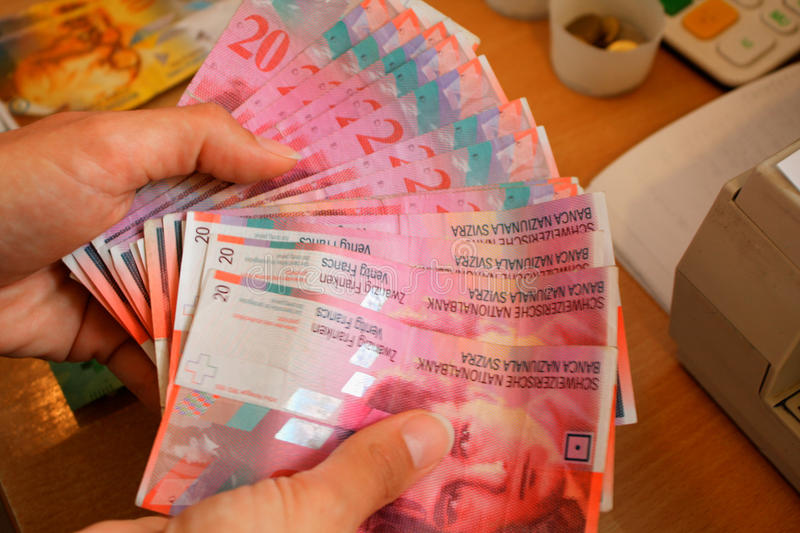 Woman showing Swiss currency bank notes royalty free stock photo