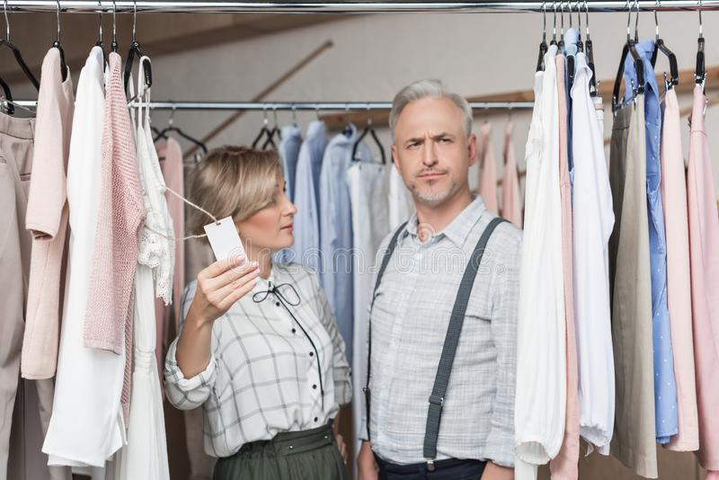 Woman showing a tag to man. At the shop royalty free stock photos