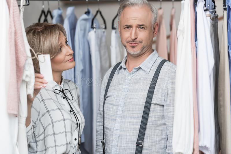 Woman showing a tag to man. Woman showing a tag to men at the store royalty free stock photography