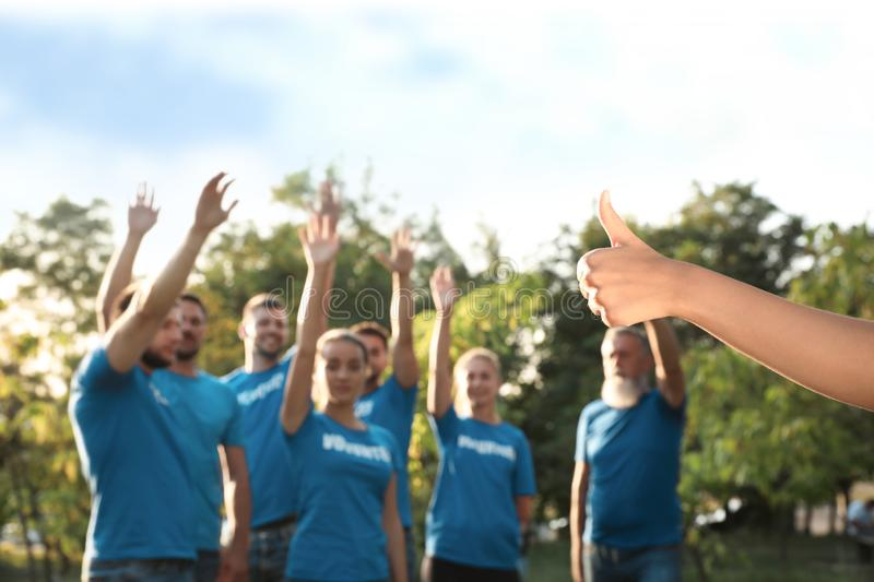 Woman showing thumb up at volunteers meeting. Group of people stock photography