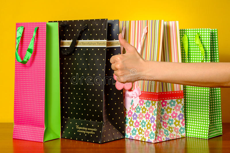 Woman showing thumbs up. Concept success, shopping bags on the background. stock image