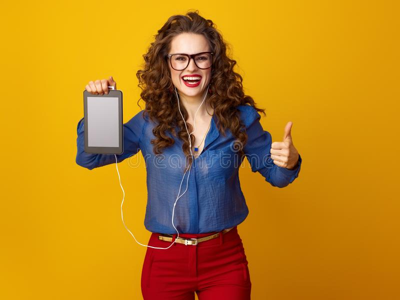 Woman showing thumbs up and listening to music with headphone stock photo