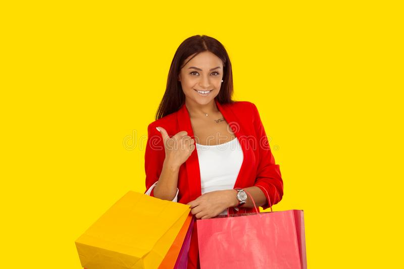 Woman showing thumbs up sign holdingshopping bags stock photo