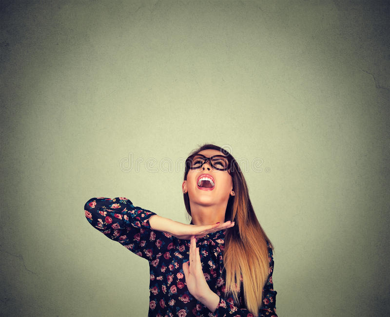 Woman showing time out hand gesture, frustrated screaming to stop. Young woman showing time out hand gesture, frustrated screaming to stop isolated on grey wall royalty free stock image