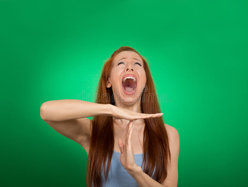 Woman showing time out hand gesture, frustrated screaming. Young woman showing time out hand gesture, frustrated screaming to stop on green background. Too many stock photography