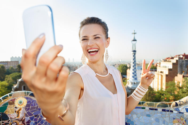 Woman showing victory and taking selfie with mobile, Park Guell. Refreshing promenade in unique Park Guell style in Barcelona, Spain. Portrait of smiling young stock photography