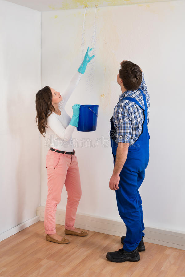 Woman Showing Water Leaking From Ceiling To Maintenance Guy. Young Woman With Bucket Showing Water Leaking From Damage Ceiling To Maintenance Guy stock photos