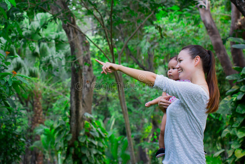 Woman shows a baby around the lush rainforest and the sights it has to offer royalty free stock photography