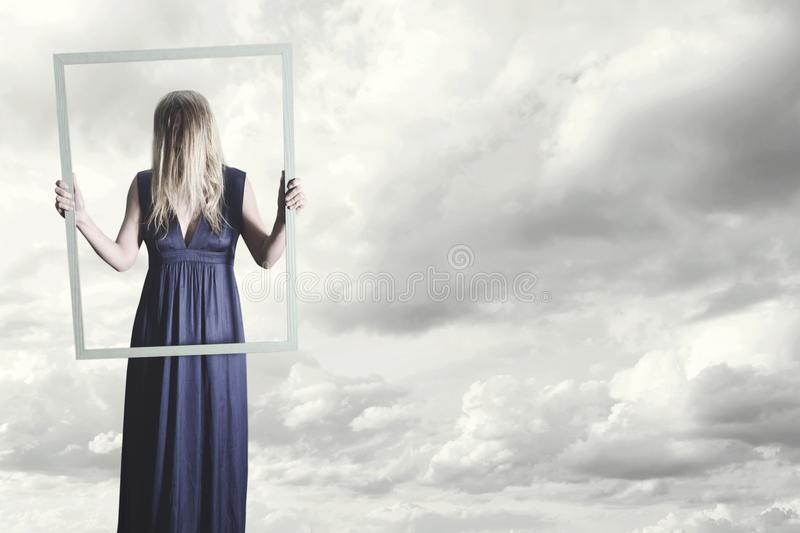 woman shows herself in the frame of a painting with her hair covering her face royalty free stock photos