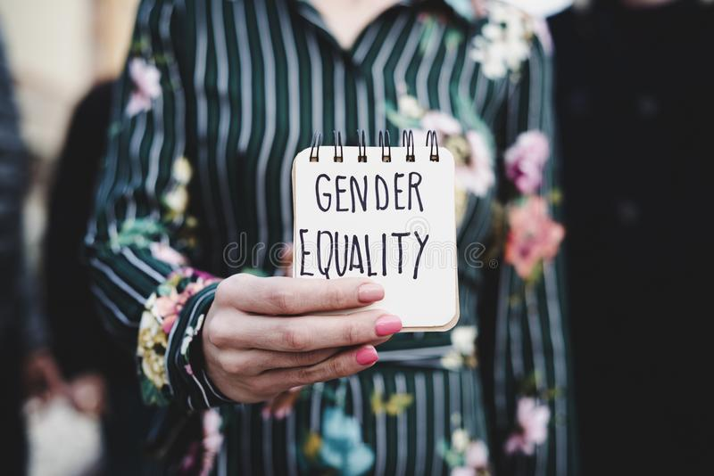 Woman shows notepad with the text gender equality. Closeup of a young woman outdoors showing a notepad in front of her with the text gender equality written in royalty free stock image