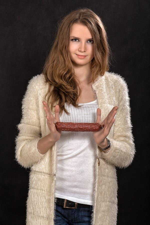 Woman shows sausage royalty free stock image