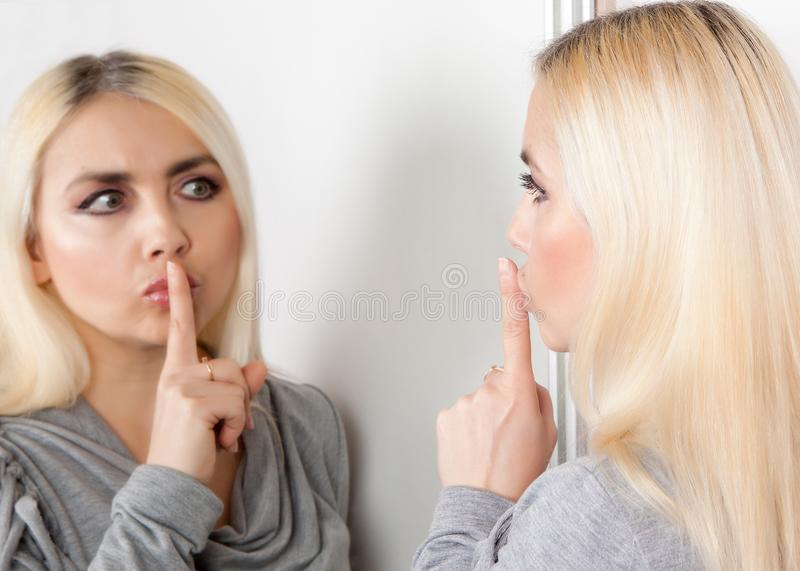 Woman shows silence sign looking at her reflection in the mirror stock photo