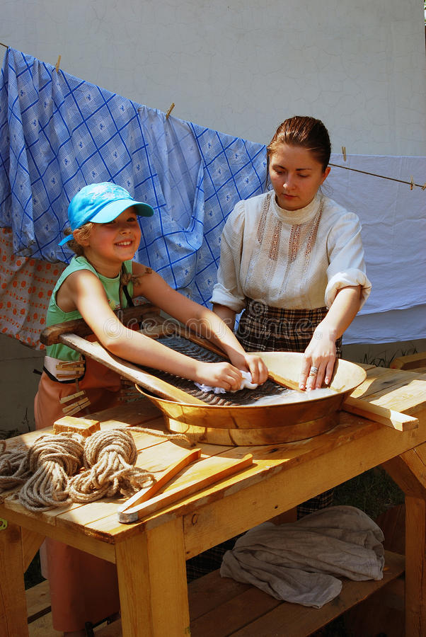A woman shows to a girl how to wash clothes using vintage tools. royalty free stock image