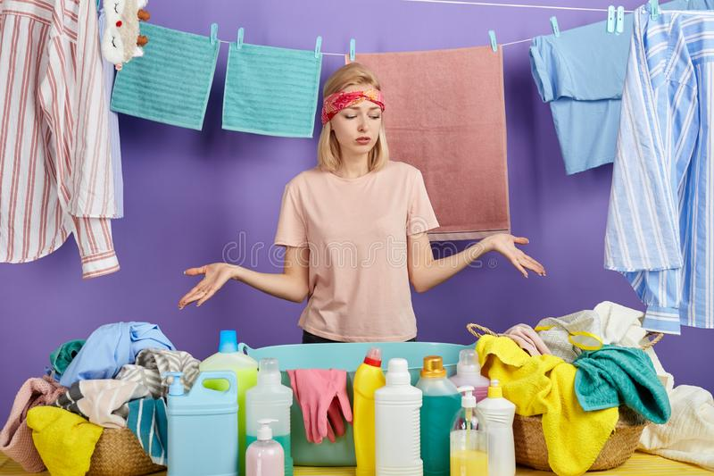 Woman shrugging shoulders being sad not knowing how to wash all clothes. Beautiful fair-haired woman shrugging shoulders being sad not knowing how to wash all royalty free stock image