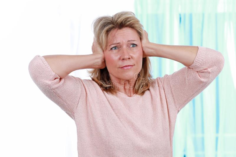 Woman shut her ears from noise. Mature woman keep her hands very firmly over her ears to prevent her ears from noise royalty free stock photo