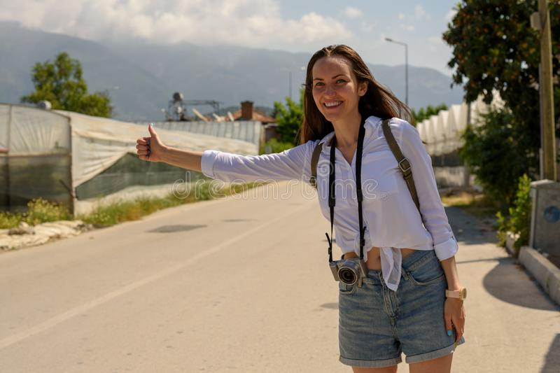 A woman on the side of the road catches a passing car, hitchhiking royalty free stock photography