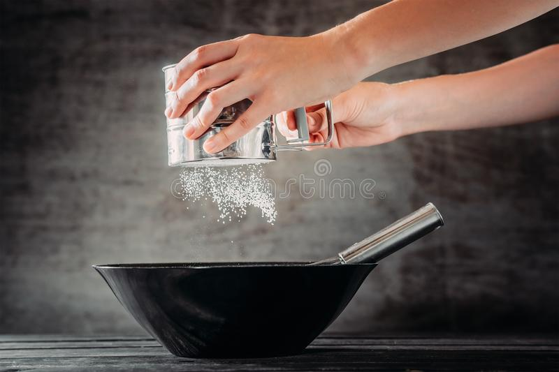 Woman sifting flour with sieve in black bowl. On wooden table stock image