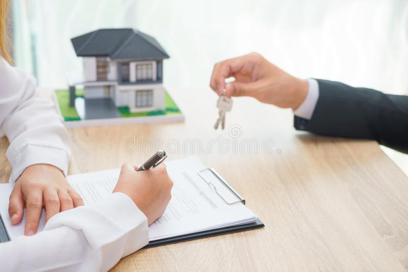 Woman sign approved loan agreement while usinessman or sale man. Giving a house key - buying home concept royalty free stock photos