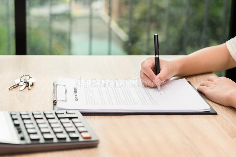 Woman signing car agreement contract with key and calculator on. Wooden desk royalty free stock images