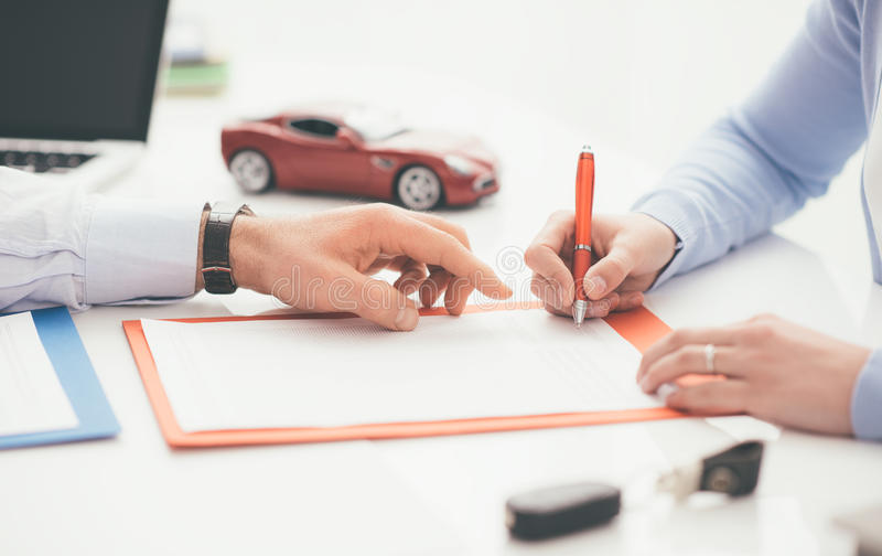 Driver signing a car insurance. Woman signing a car insurance policy, the agent is pointing at the document royalty free stock photography
