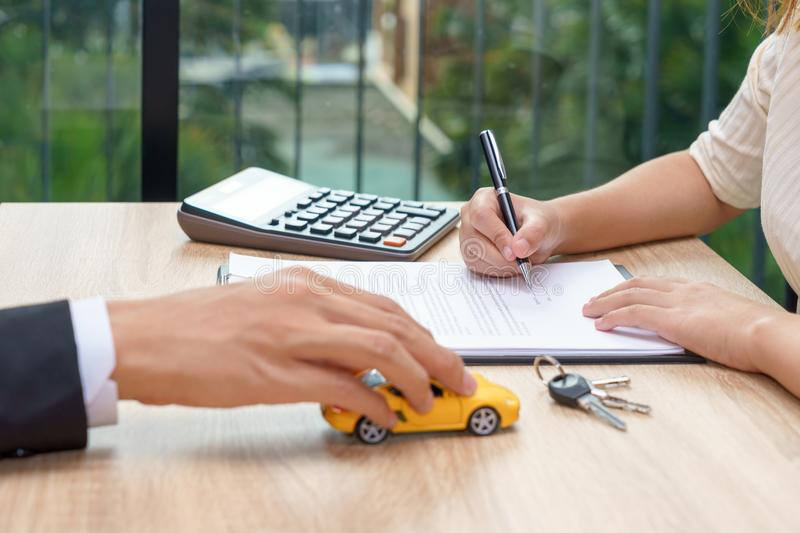 Woman signing car loan agreement contract with car key and calculator on wooden desk. Woman signing car loan agreement contract with car key and calculator on stock images
