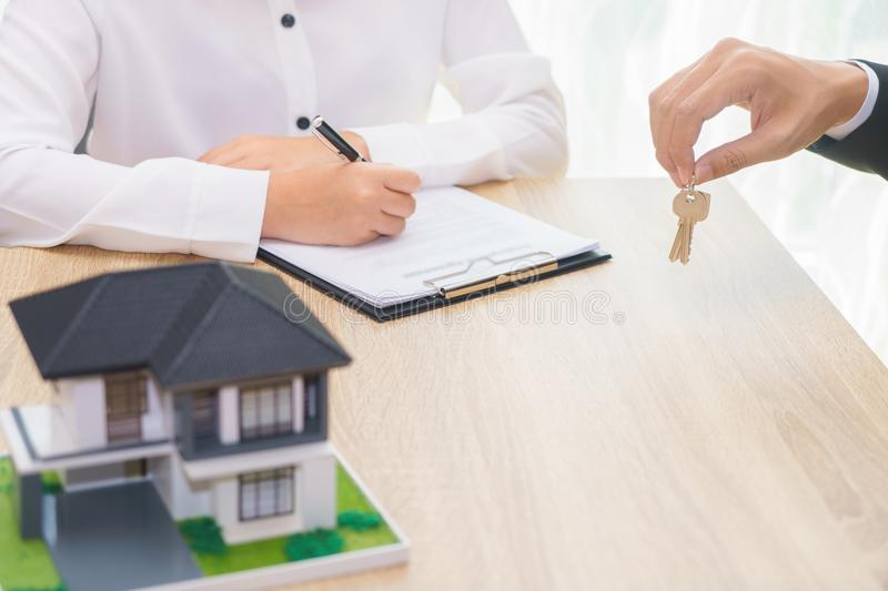 Woman signing contract or home loan agreement document with businessman giving a key. Woman signing contract or home loan agreement document with businessman stock photos