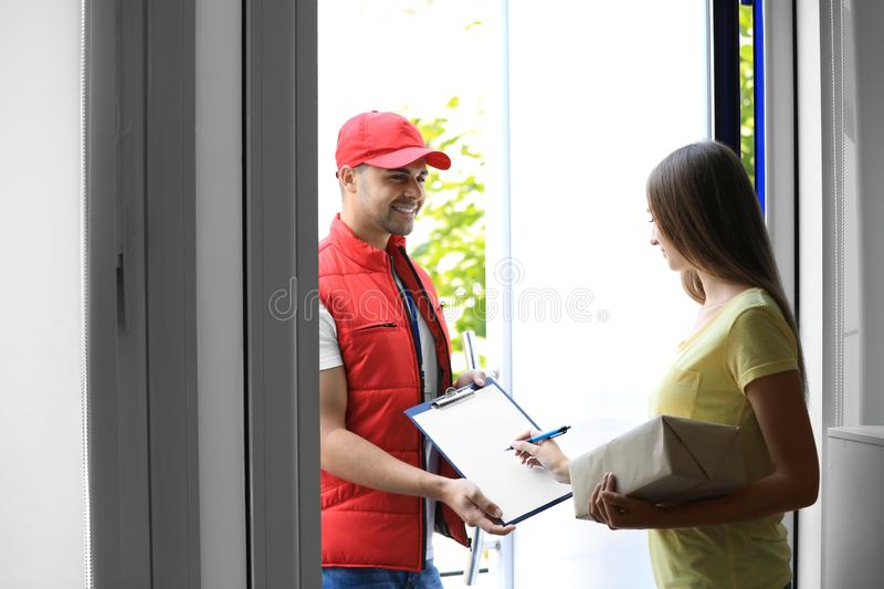 Woman signing for delivered parcel. Courier service. Woman signing for delivered parcel on doorstep. Courier service royalty free stock images