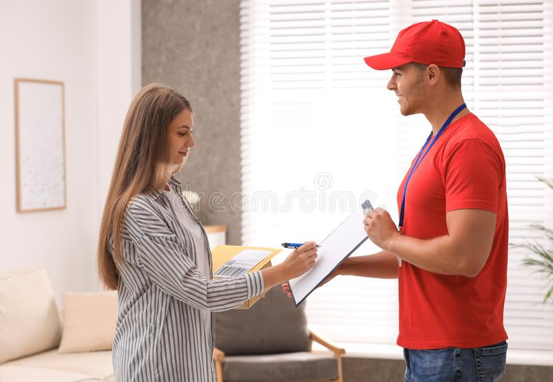 Woman signing for delivered parcels. Courier service. Woman signing for delivered parcels at home. Courier service stock images