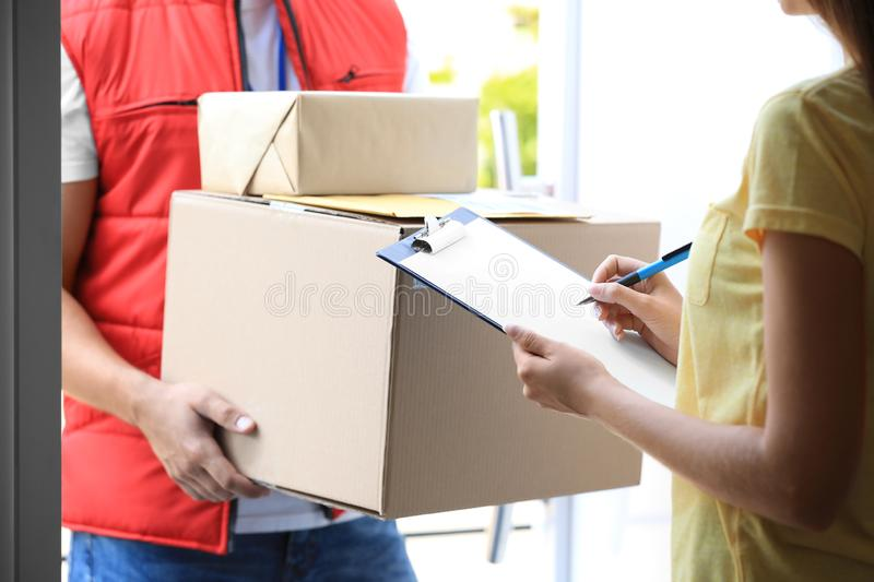 Woman signing for delivered parcels on doorstep. Courier service. Woman signing for delivered parcels on doorstep, closeup. Courier service stock photography