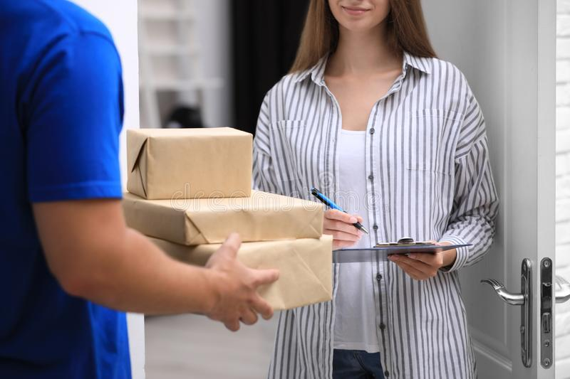 Woman signing for delivered parcels on doorstep. Closeup royalty free stock photos