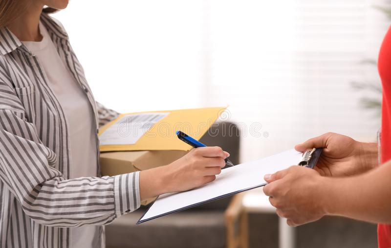Woman signing for delivered parcels at home. Courier service. Woman signing for delivered parcels at home, closeup. Courier service stock photos