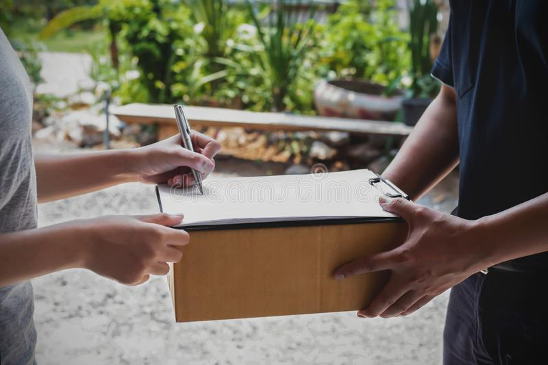 The woman is signing the documents the delivery staff gave To confirm parcel receipt - delivery service concept stock image