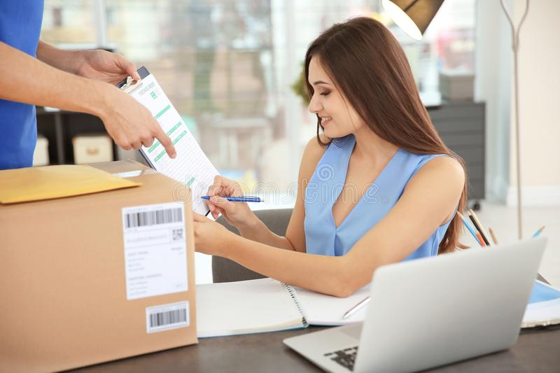 Woman signing documents. After receiving parcel from courier royalty free stock photos