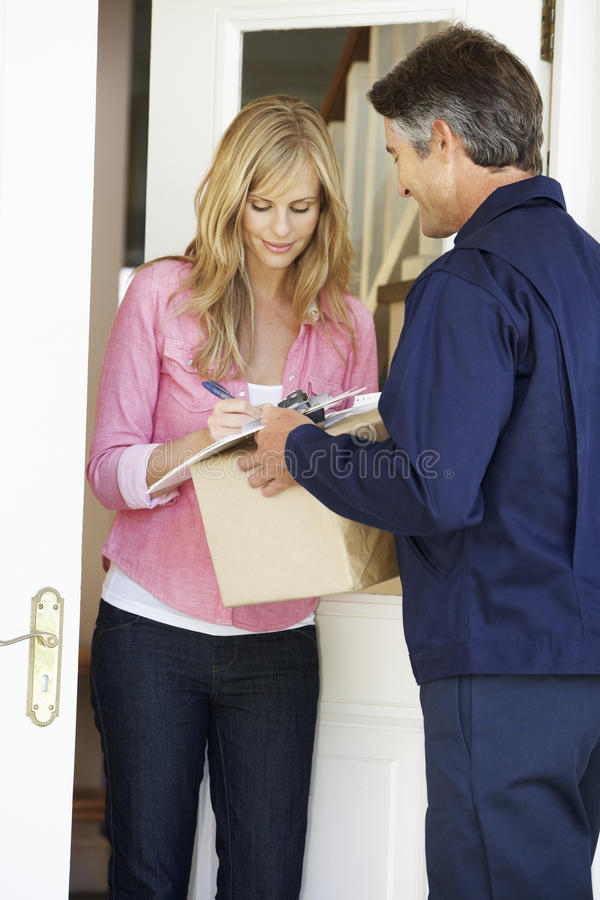 Woman Signing For Package Delivered By Courier stock images