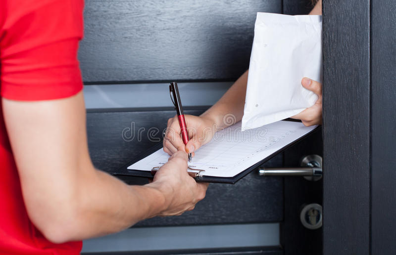 Woman signing package delivery papers. Woman signing parcel shipment documents on clipboard royalty free stock image